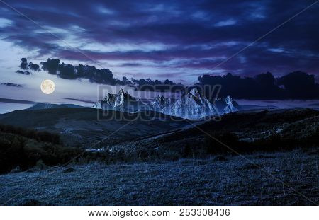 Composite Of Countryside At Night In Full Moon Light. Gorgeous Cloudscape Over The Mountains With Ro