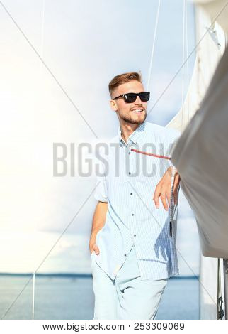 Relaxing Man Happily On The Vacation Sailboat Yacht Standing On A Deck.