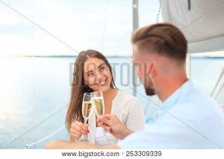 Smiling Young Couple With Champagne And Looking At Each Other While Sitting On The Board Of Yacht.