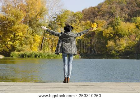 Girl In A Hat With Leaves In Hands Standing On The Dock. Autumn, Sunny. Back View