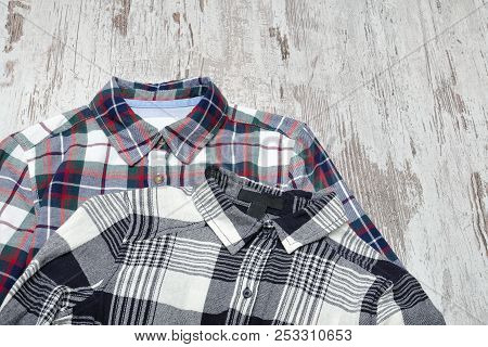 Two Checkered Shirts On Wooden Background. Fashionable Concept