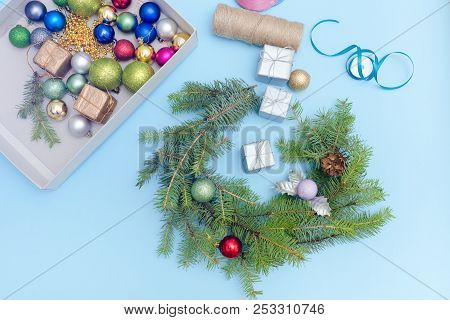 Making A Christmas Wreath. Christmas Balls, Ribbon And Boxes. Blue Background.