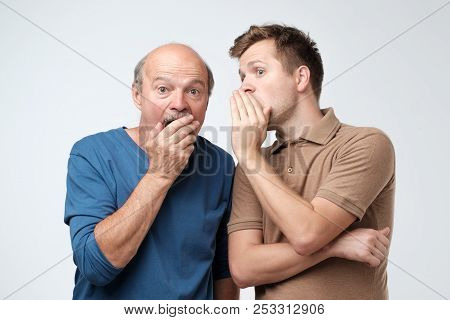 Young Caucasian Son Telling Secret To His Senior Father. Senior Man In Shock Opening His Mouth.