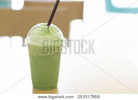 Closeup Plastic Glass Of Ice Matcha Frappe On Wood Table With Over Light From Out Door, Selective Fo