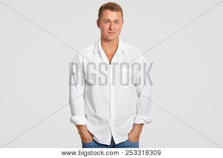Handsome Young Male In White Shirt, Keeps Hands In Pockets, Looks Directly At Camera, Has Serious Co