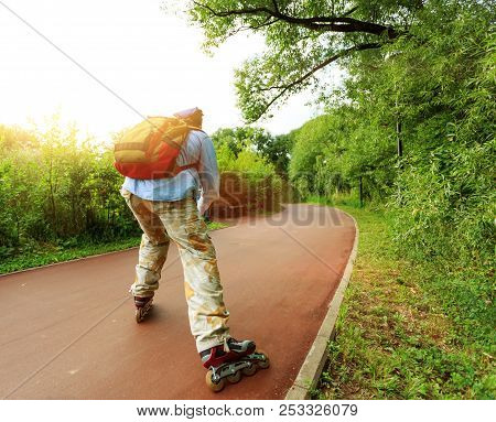 Young Man Rollerskating In Park. Concept Of Healthy Lifestyle