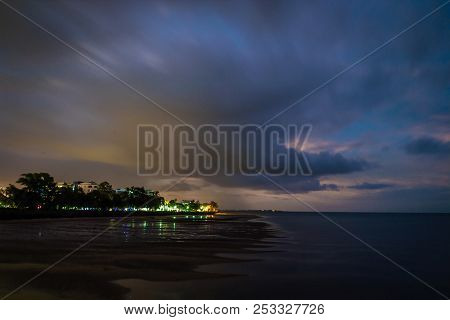 Urangan At Night With Lights On And Red Clouds