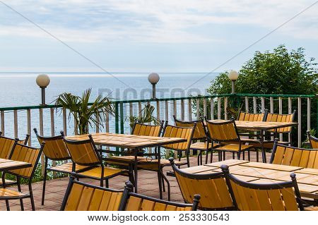 Terrace With Wooden Tables And Chairs With Sea View In Sunny Summer Day