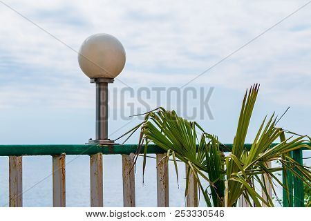 Lamppost On Railing And Leaves Of Palm Closeup On The Background Of Cloudy Sky