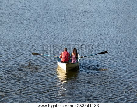 Couple In Love Sailing On A Rowing Boat In Summer. Young Man And Woman In A Boat, Romantic Date