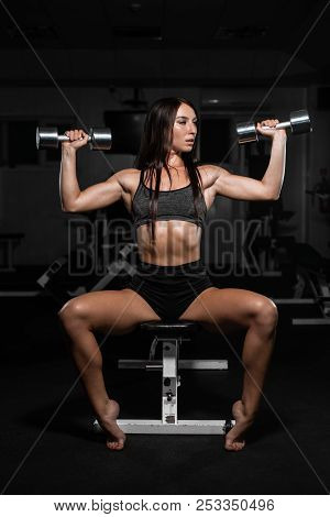 Beautiful Muscular Woman Training With Dumbbells, Girl Pumps Her Deltoid Muscle