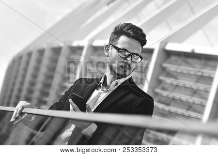 Modern Businessman. Confident Young Man In Full Suit Standing Outdoors With Cityscape In The Backgro