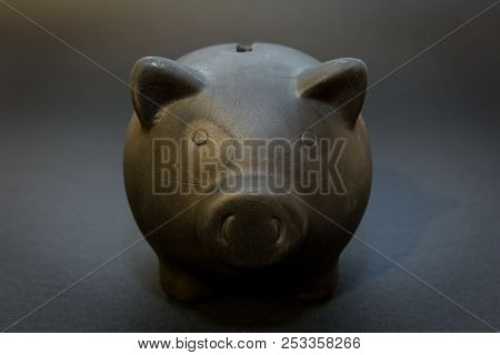 Front Of The Black Piggy Bank On The Black Background, The Symbol Of Saving For A Rainy Day