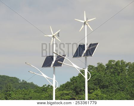 Street lights powered by solar and wind energy on the cloudy sky and woods background