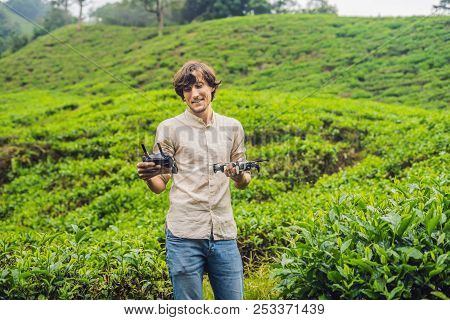 Men tourist tries to launch the drone at a tea plantation. Natural selected, Fresh tea leaves in tea farm in Cameron Highlands, Malaysia. Ecotourism concept poster