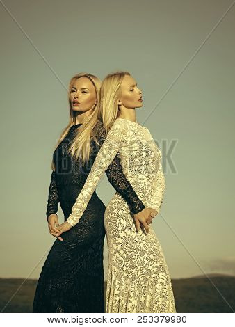 Women Wearing Black And White Dresses. Opposites And Contrasts Concept. Two Girls With Long Blond Ha