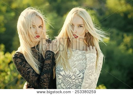 Beauty And Fashion. Two Women With Red Lips And Long Blond Hair. Contrasts And Opposites Concept. Du