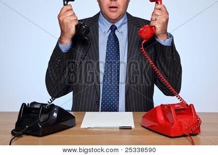 Photo of a businessman sat at a desk with two traditional telephones, one red and one black. Both handsets are raised and he doesn't know who to talk to first.