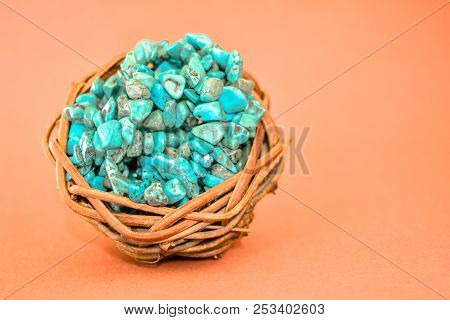 Pile Stones Of Raw Turquoise In Small Wooden Nest On A Brown Background. Blue And Green Color Stones