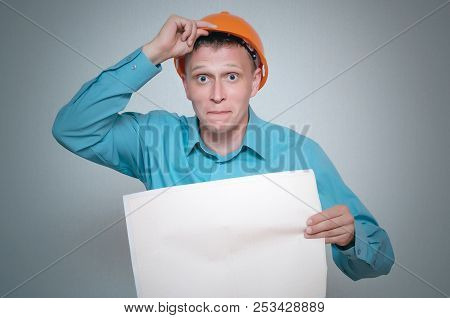 Confused Builder Construction Worker Is Holding In Hand A Plan Draft Document Isolated On Gray Backg