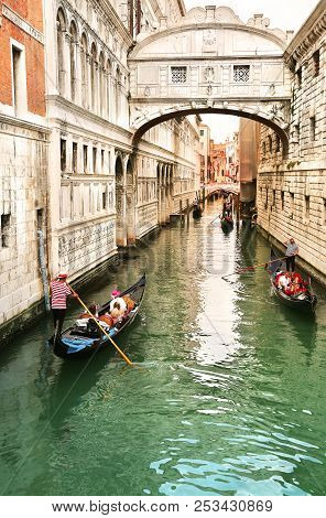 Venice, Italy, Jun 8, 2018: View Of Bridge Of Sighs With Gondoliers Carrying Tourists In Their Gondo
