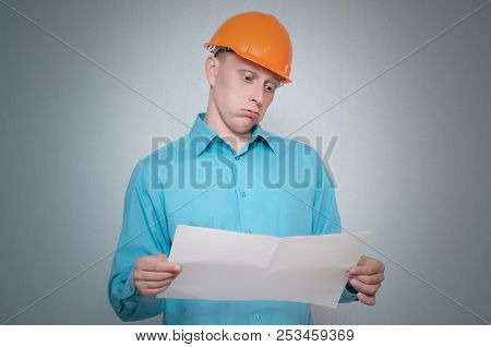 Perplexed Builder Construction Worker Is Holding In Hand A Plan Draft Document Isolated On Gray Back