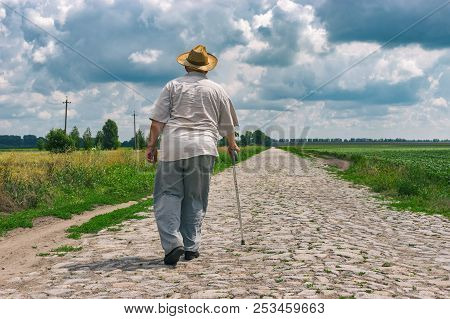 Senior Man With Walking Stick Wearing Straw Hat Goes Home On A Cobblestone Road In Central Ukraine