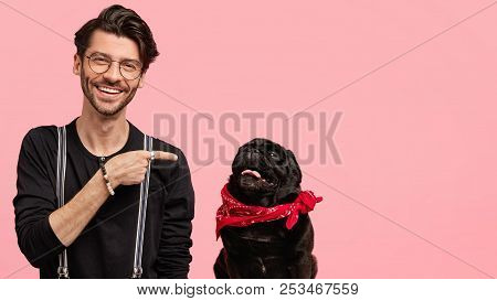 Studio Shot Of Happy Caucasian Male Has Bristle, Points At His Favourite Dog, Expresses Care And Lov