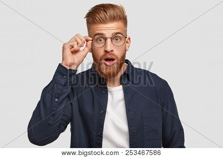 Stupefied Hipster Guy With Shocked Expression, Hears Something Unbelievable, Keeps Hand On Rim Of Ro
