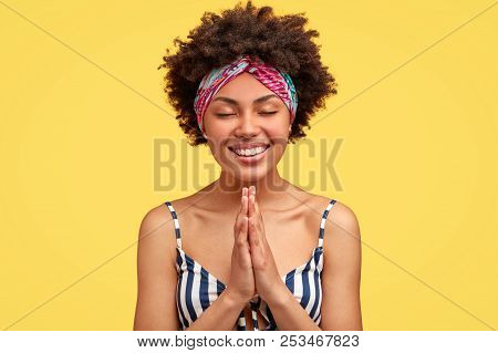 Cute Happy African American Woman Keeps Hands In Praying Gesture, Has Broad Smile, Prays Before Impo