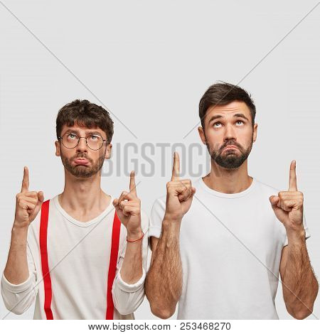 Two unhappy bearded young guys have displeased expressions, point with both index fingers above, show free space for your advertisement or promotional text, have sullen looks. Teamwork concept poster