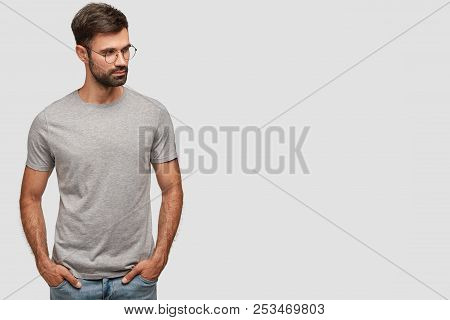 Horizontal Shot Of Serious Unshaven Male In Casual Grey T Shirt, Keeps Hands In Pockets, Looks Aside