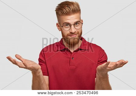 Doubtful Attractive Bearded Young Male With Ginger Hair, Thick Beard And Mustache, Shruggs Shoulders