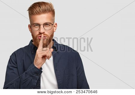 Secret Ginger Young Man Has Mysterious Expression, Touches Lips With Fore Finger, Dressed Casually,