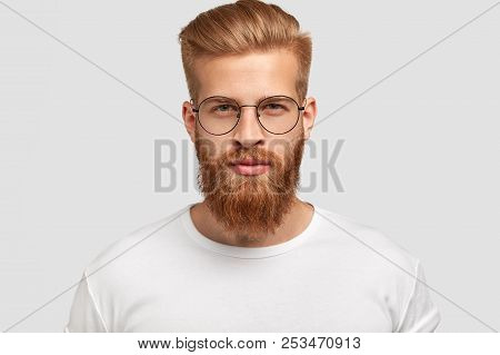 Headshot Of Attractive Serious Caucasian Male With Thick Ginger Beard And Trendy Haircut, Dressed In