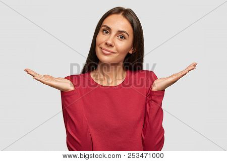 Shocked European young attractive female with dark hair, keeps hand near mouth, stares with bugged eyes as hears awful news from interlocutor, wears red sweater, isolated over white background. poster