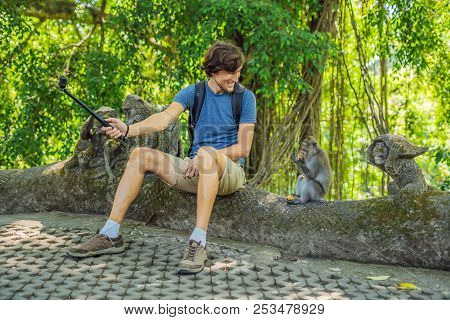 Selfie With Monkeys. Young Man Uses A Selfie Stick To Take A Photo Or Video Blog With Cute Funny Mon