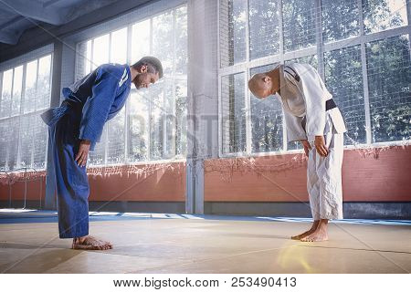 Two Judo Fighters Or Athletes Greeting Each Other In A Bow Before Practicing Martial Arts In A Fight
