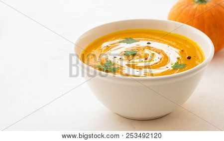 Pumpkin Soup With Cream And Pumpkin Seeds Isolated On White Background. Autumn Concept.