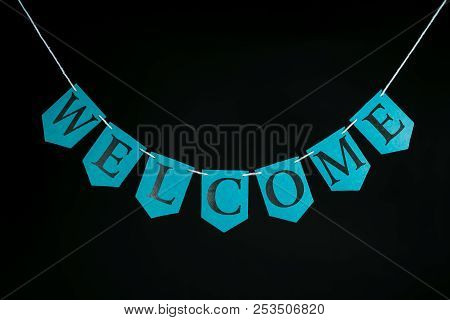 Welcome Home Banner. Blue Greeting Letters Hanging On Bunting. Welcoming Text On String Against Blac
