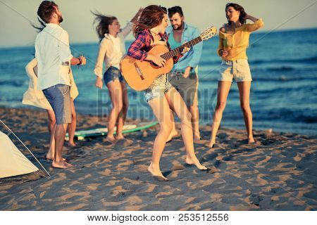 Summer, holidays, vacation, music, happy people concept - happy young people dancing together at the beach on beautiful summer sunset