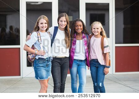 Group of pre-adolescent school kids smiling while smiling together at school. Back to school photo of a group of girls