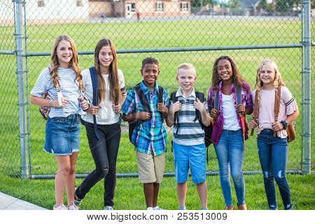 Group of school kids smiling while standing together in an elementary school playground. Back to school photo