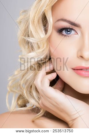 Beauty portrait of attractive blond woman with curly hair and a beautiful hairstyle. Makeup and cosmetics, face lifting and beauty concept.