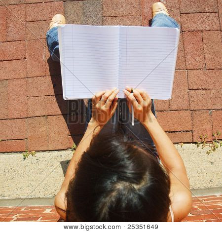 Girl writing in notebook in the city.