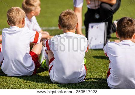 Football Coach Coaching Kids Using Tactic Strategy Whiteboard. Soccer Coach Explaining Match Tactics