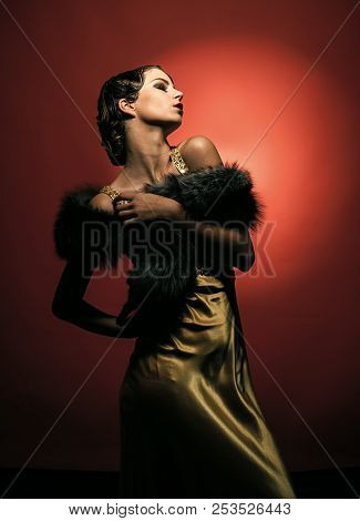 Girl In Fashionable Yellow Dress And Fur. Pin Up Pretty Fashion Model Pose On Red Background. Beauty