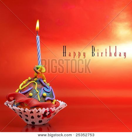 a plasticine cupcake with a candle on a red background with sentence happy birthday