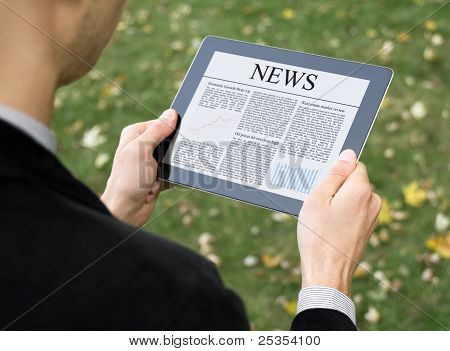 Businessman reading news on digital tablet at park. poster