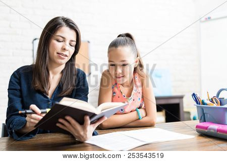 Female Student Listening To Private Teacher Reading Book At Table In Home